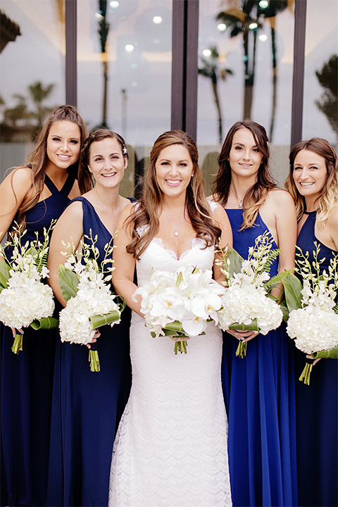 Huntington beach wedding at the hilton waterfront resort bride form fitting lace gown with a plunging neckline and thin straps with lace detail and low back design holding white and green floral bridal bouquet with bridesmaids long navy blue dresses holding white and green floral bouquets
