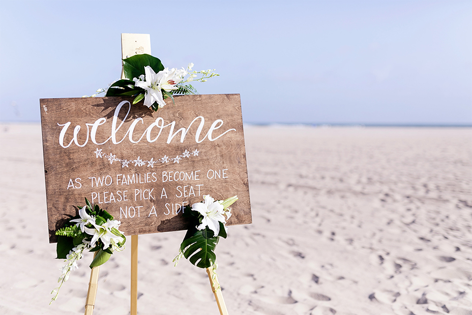 Huntington beach wedding at the hilton waterfront resort wedding ceremony altar with brown wood and white and green flower decor on sand wedding photo idea for ceremony altar and welcome sign rustic decor light brown wood sign with white calligraphy writing and white and green flower decor