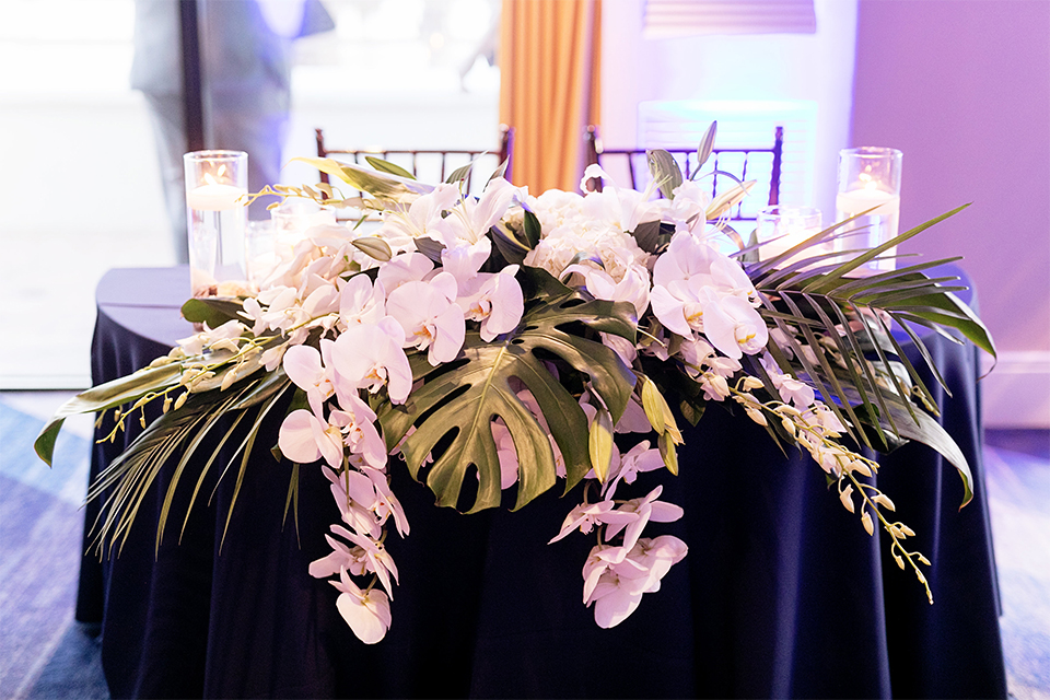 Huntington beach wedding at the hilton waterfront resort table set up white table linen with white and green floral centerpiece decor with white table numbers written on green leaves and glass candle decor with dark chairs