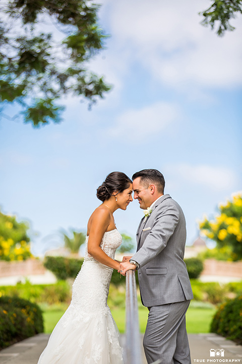 skybox-venue-wedding-bride-and-groom-touching-heads-bride-in-strapless-gown-with-beaded-bodice-groom-in-light-grey-suit-with-ivory-tie