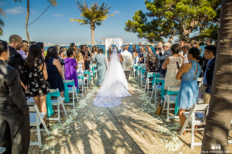 San diego outdoor wedding at bali hai bride ball gown with thin lace straps and a sweetheart neckline with lace and beading detail on bodice with long veil walking down aisle with parents