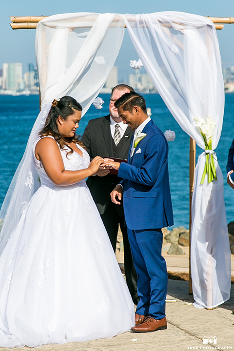 San diego outdoor wedding at bali hai bride ball gown with thin lace straps and a sweetheart neckline with lace and beading detail on bodice with long veil with groom cobalt blue notch lapel suit with white dress shirt and white vest with long white striped tie and pocket square with white floral boutonniere exchanging rings during ceremony