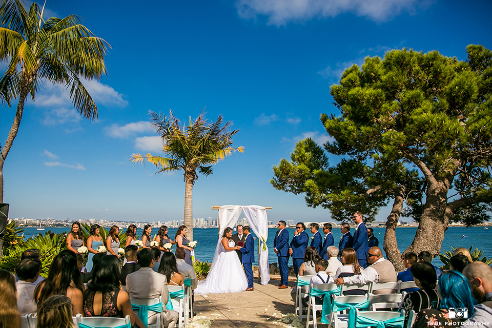 San diego outdoor wedding at bali hai bride ball gown with thin lace straps and a sweetheart neckline with lace and beading detail on bodice with long veil with groom cobalt blue notch lapel suit with white dress shirt and white vest with long white striped tie and pocket square with white floral boutonniere holding hands during ceremony