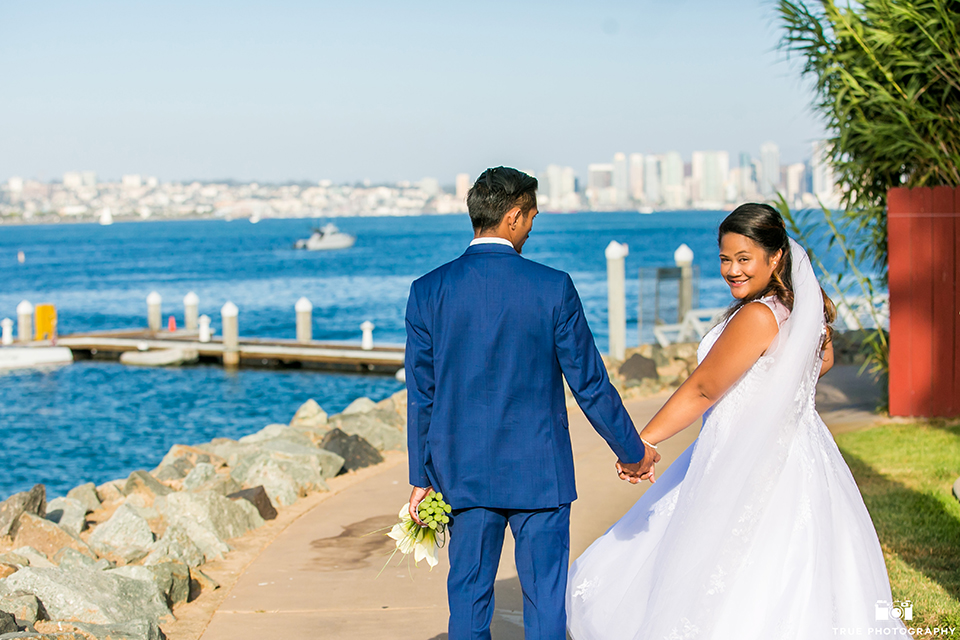 San diego outdoor wedding at bali hai bride ball gown with thin lace straps and a sweetheart neckline with lace and beading detail on bodice with long veil with groom cobalt blue notch lapel suit with white dress shirt and white vest with long white striped tie and pocket square with white floral boutonniere walking and holding hands