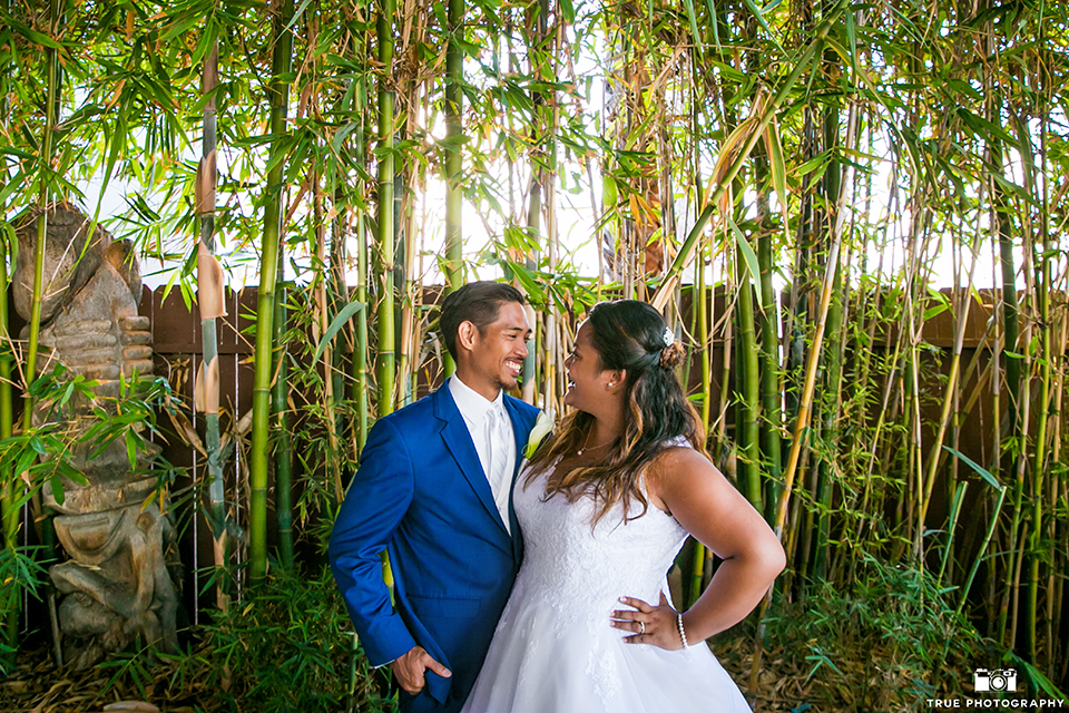 San diego outdoor wedding at bali hai bride ball gown with thin lace straps and a sweetheart neckline with lace and beading detail on bodice with long veil with groom cobalt blue notch lapel suit with white dress shirt and white vest with long white striped tie and pocket square with white floral boutonniere hugging and smiling