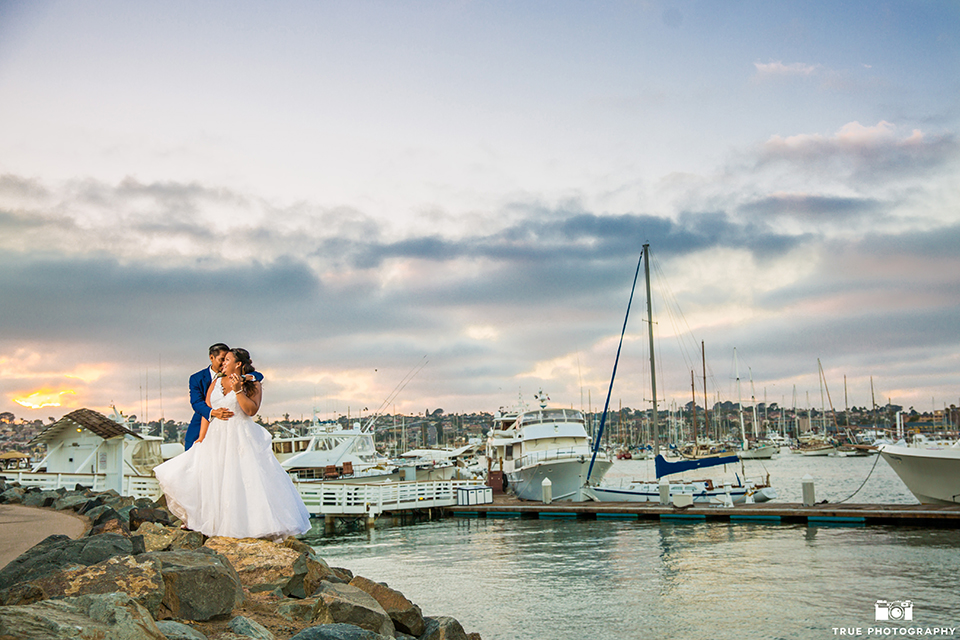 San diego outdoor wedding at bali hai bride ball gown with thin lace straps and a sweetheart neckline with lace and beading detail on bodice with long veil with groom cobalt blue notch lapel suit with white dress shirt and white vest with long white striped tie and pocket square with white floral boutonniere hugging far away