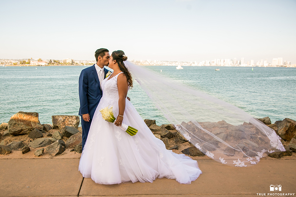 San diego outdoor wedding at bali hai bride ball gown with thin lace straps and a sweetheart neckline with lace and beading detail on bodice with long veil with groom cobalt blue notch lapel suit with white dress shirt and white vest with long white striped tie and pocket square with white floral boutonniere standing and kissing