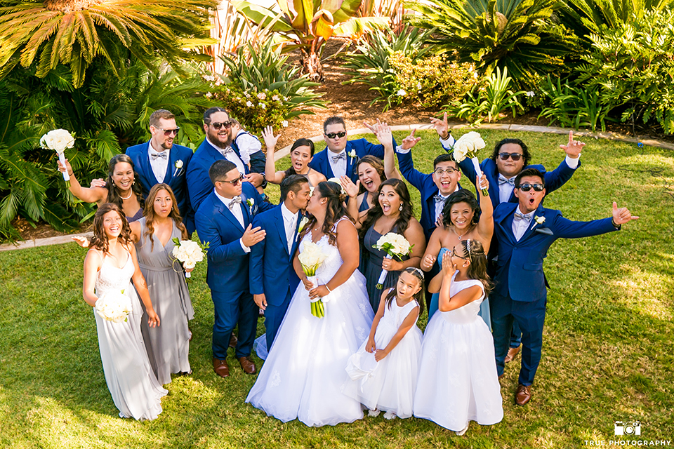 San diego outdoor wedding at bali hai bride ball gown with thin lace straps and a sweetheart neckline with lace and beading detail on bodice with long veil with groom cobalt blue notch lapel suit with white dress shirt and white vest with long white striped tie and pocket square with white floral boutonniere kissing with wedding party cheering