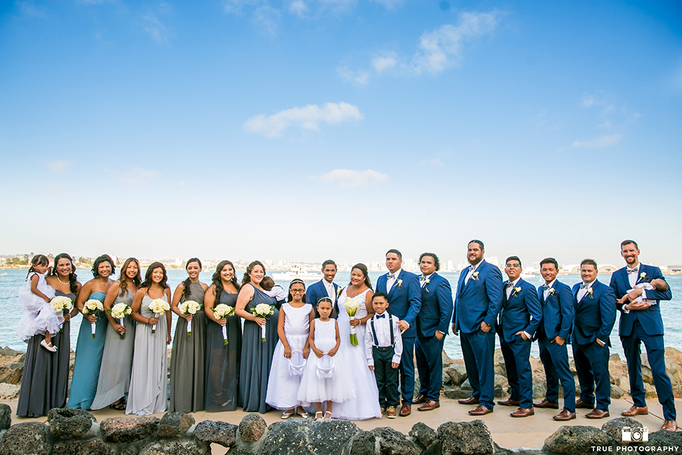 San diego outdoor wedding at bali hai bride ball gown with thin lace straps and a sweetheart neckline with lace and beading detail on bodice with long veil with groom cobalt blue notch lapel suit with white dress shirt and white vest with long white striped tie and pocket square with white floral boutonniere with wedding party bridesmaids mix and matched dresses and groomsmen