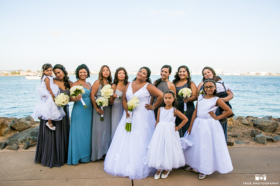 San diego outdoor wedding at bali hai bride ball gown with thin lace straps and a sweetheart neckline with lace and beading detail on bodice with long veil holding white floral bridal bouquet with bridesmaids long mix and matched dresses