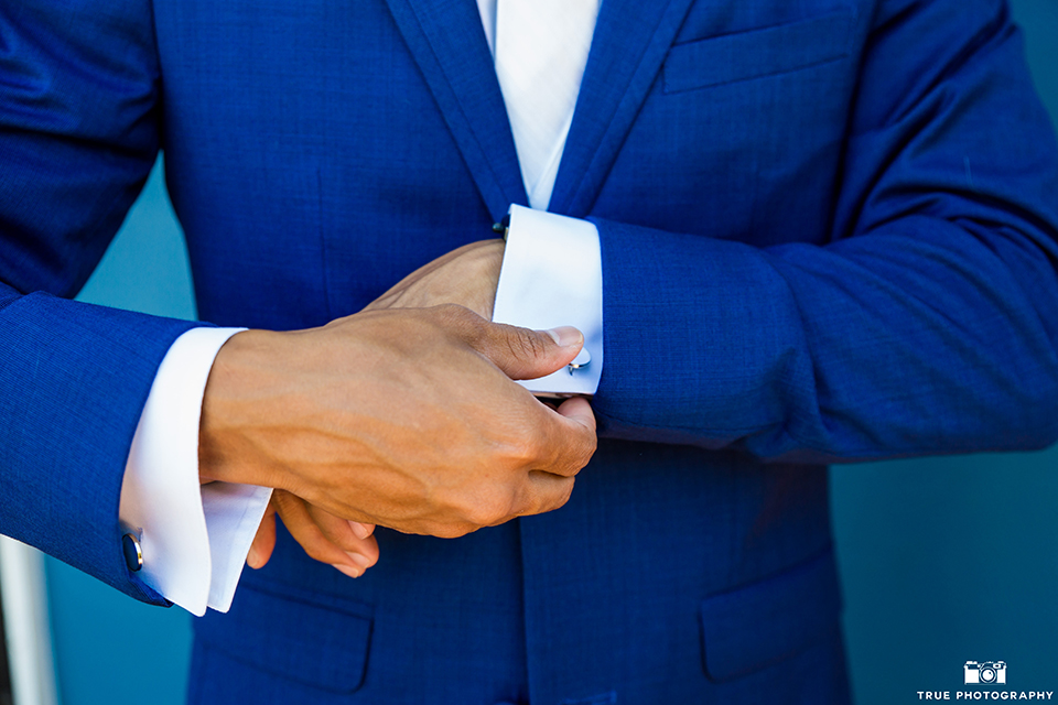 San diego outdoor wedding shoot at bali hai groom cobalt blue notch lapel suit with a white dress shirt and white vest with a long white striped tie and pocket square close up holding sleeve
