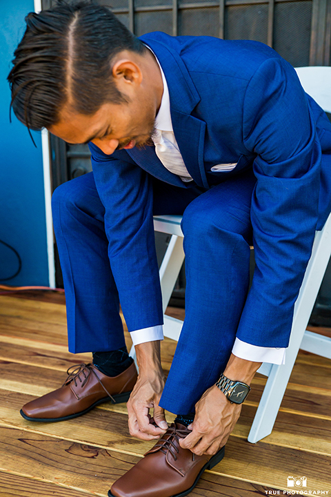 San diego outdoor wedding shoot at bali hai groom cobalt blue notch lapel suit with a white dress shirt and white vest with a long white striped tie and pocket square putting on shoes getting ready before ceremony