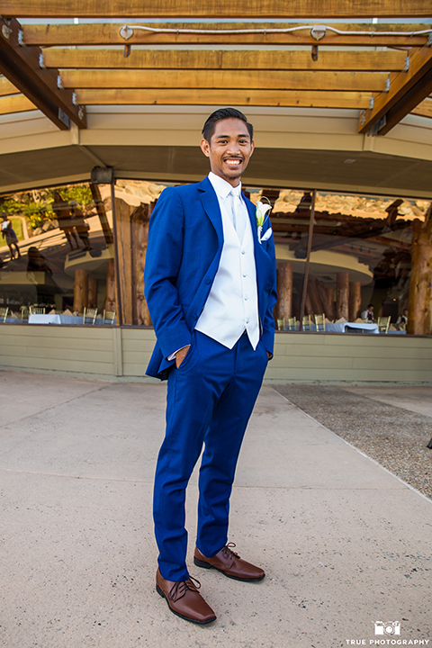 San diego outdoor wedding shoot at bali hai groom cobalt blue notch lapel suit with a white dress shirt and white vest with a long white striped tie and pocket square with white floral boutonniere standing with hands in pockets