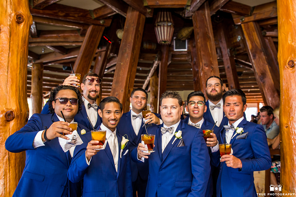 San diego outdoor wedding shoot at bali hai groom cobalt blue notch lapel suit with a white dress shirt and white vest with a long white striped tie and pocket square with white floral boutonniere with groomsmen cobalt blue suits with bow ties holding drinks