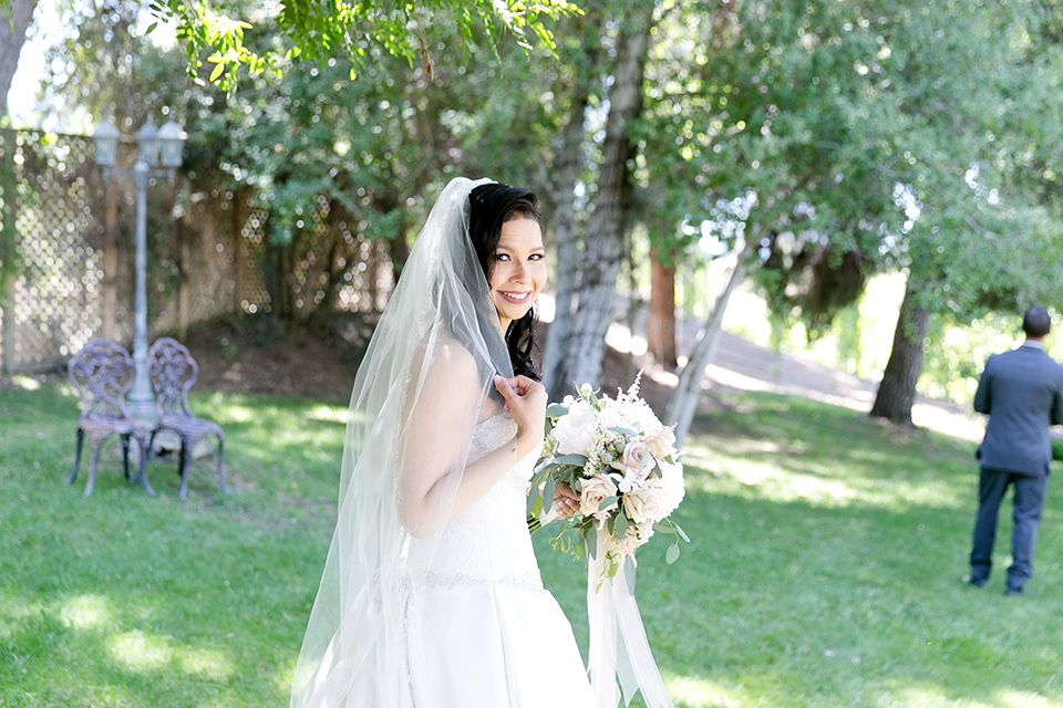 Temecula outdoor wedding at lake oak meadows bride a line strapless gown with lace and detail beading on bodice and long veil holding white and green floral bridal bouquet first look behind groom wedding photo idea for first look