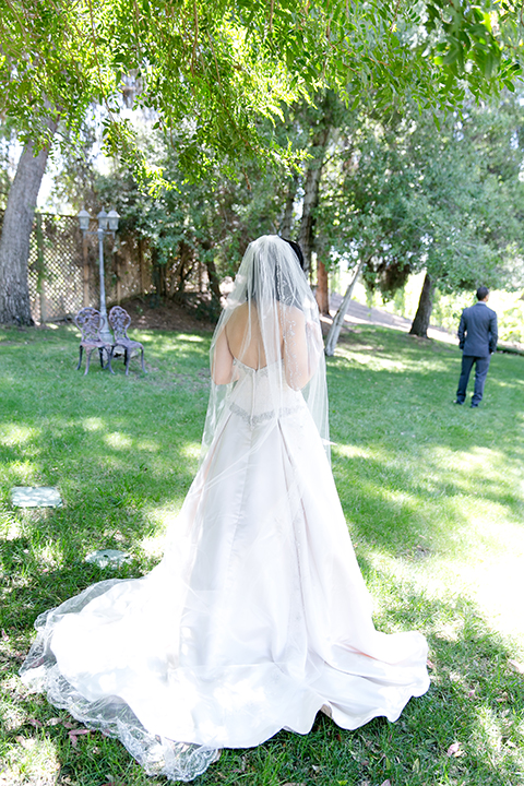 Temecula outdoor wedding at lake oak meadows bride a line strapless gown with lace and detail beading on bodice and long veil with groom grey notch lapel suit with light grey vest and white dress shirt with light grey matching bow tie and white floral boutonniere first look bride behind groom