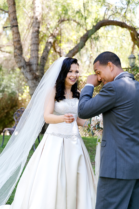 Temecula outdoor wedding at lake oak meadows bride a line strapless gown with lace and detail beading on bodice and long veil with groom grey notch lapel suit with light grey vest and white dress shirt with light grey matching bow tie adn white floral boutonniere first look groom crying