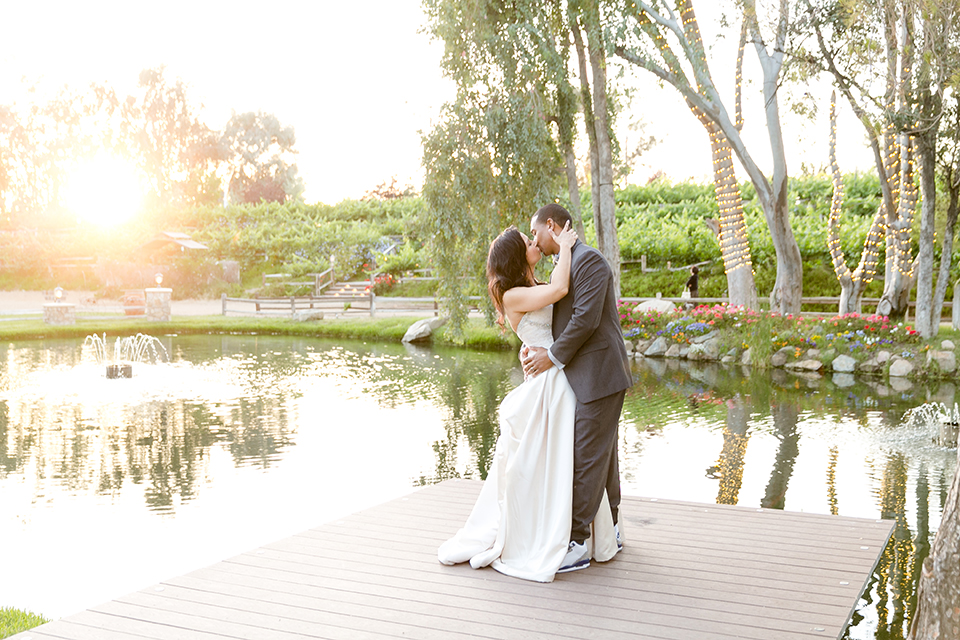 Temecula outdoor wedding at lake oak meadows bride a line strapless gown with lace and detail beading on bodice and long veil with groom grey notch lapel suit with light grey vest and white dress shirt with light grey matching bow tie adn white floral boutonniere standing and kissing