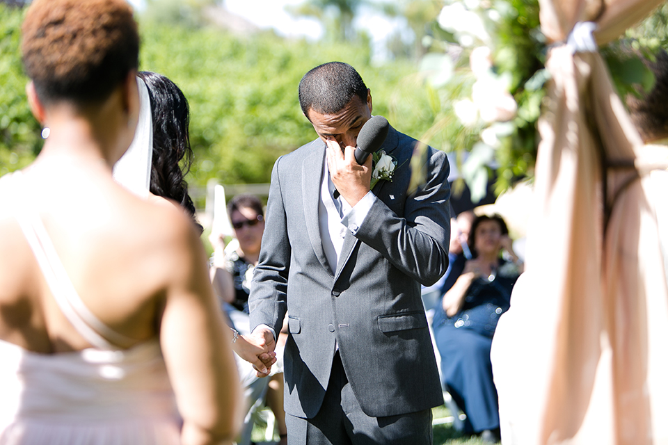 Temecula outdoor wedding at lake oak meadows bride a line strapless gown with lace and detail beading on bodice and long veil with groom grey notch lapel suit with light grey vest and white dress shirt with light grey matching bow tie adn white floral boutonniere groom crying during ceremony