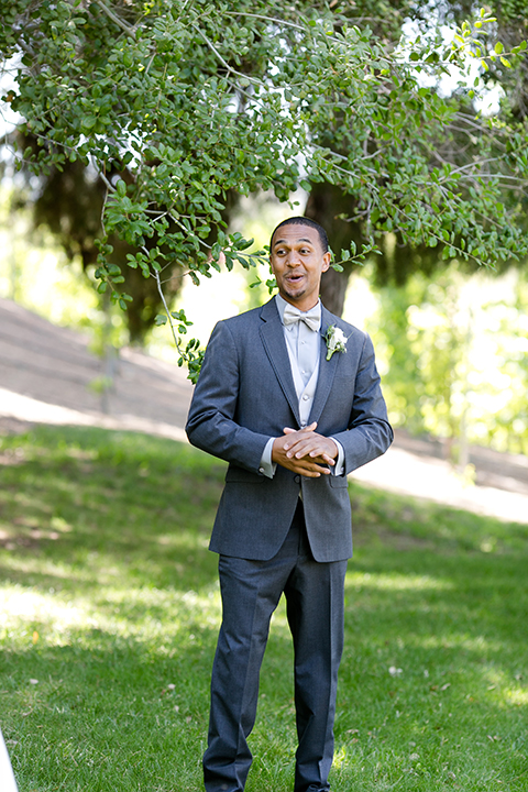 Temecula outdoor wedding at lake oak meadows groom grey notch lapel suit with light grey vest and light grey matching bow tie with white dress shirt and white floral boutonniere smiling