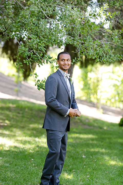Temecula outdoor wedding at lake oak meadows groom grey notch lapel suit with light grey vest and light grey matching bow tie with white dress shirt and white floral boutonniere standing and smiling