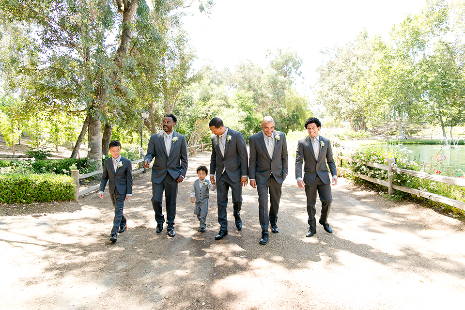 Temecula outdoor wedding at lake oak meadows groom grey notch lapel suit with light grey vest and light grey matching bow tie with white dress shirt and white floral boutonniere walking with groomsmen grey notch lapel suits with light grey vests and ties and ring bearer light grey suit