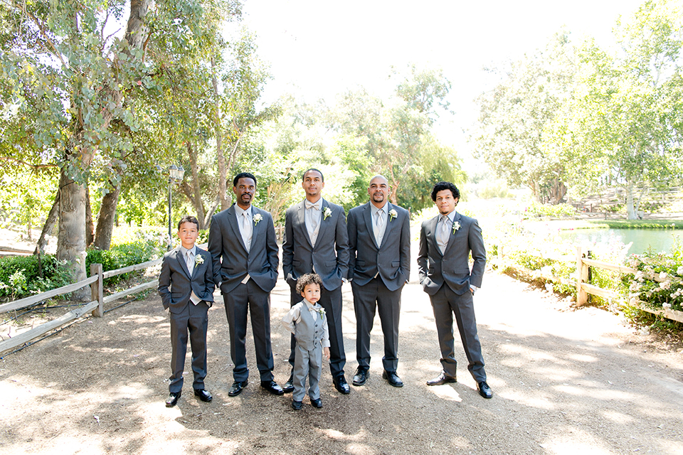 Temecula outdoor wedding at lake oak meadows groom grey notch lapel suit with light grey vest and light grey matching bow tie with white dress shirt and white floral boutonniere standing with groomsmen grey suits with light grey vests and ties and ring bearer light grey suit
