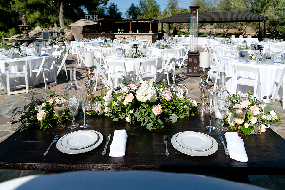 Temecula outdoor wedding at lake oak meadows table set up white table linen with white chairs and white and green flower centerpiece decor with wine cork centerpiece decor with white table numbers and candle lanterns with pictures of bride and groom
