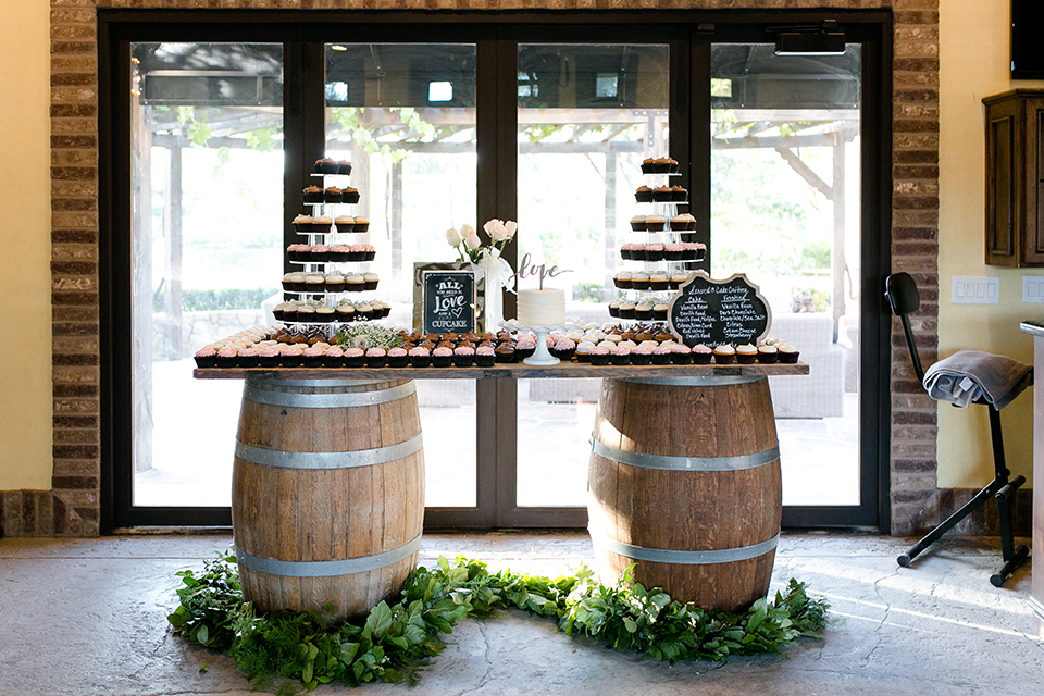 Temecula outdoor wedding at lake oak meadows dessert table assortment of sweets on two wine barrels and table with black and white sign for decor and white one tier wedding cake with gold love calligraphy cake topper with greenery floral decor