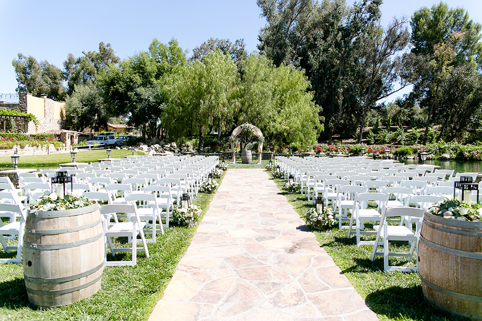 Temecula outdoor wedding at lake oak meadows ceremony set up with white chairs on grass with lanterns along aisle and white and green flower decor with floral arch and wine barrels for decor wedding photo idea for ceremony set up