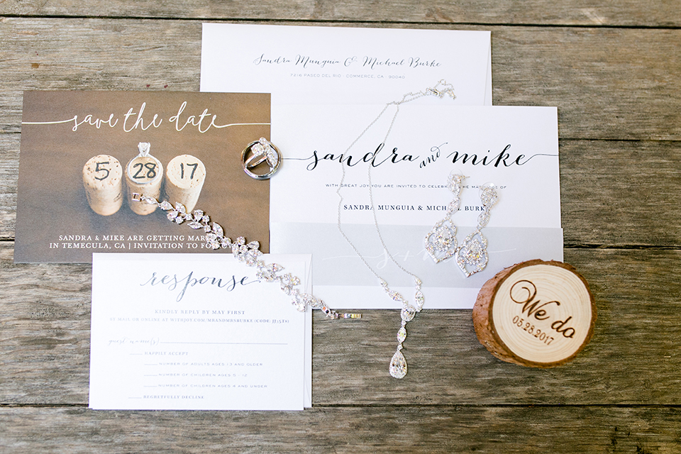 Temecula outdoor wedding at lake oak meadows wedding invitations white with black calligraphy writing and tree stump rustic decor with save the dates and bride jewelry decor on light brown wood background wedding photo idea for invitations