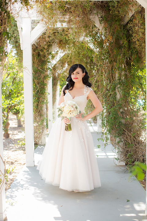 Orange county outdoor summer wedding at the heritage museum bride ball gown with lace straps and a sweetheart neckline with a short tulle skirt and long veil holding white floral bridal bouquet