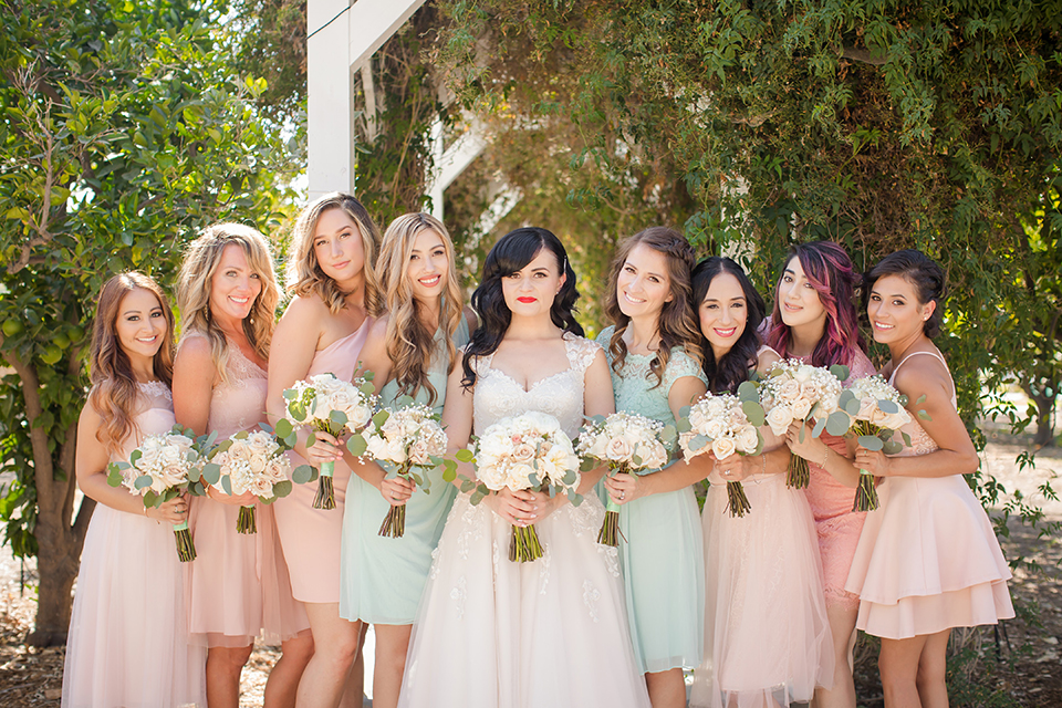 Orange county outdoor summer wedding at the heritage museum bride ball gown with lace straps and a sweetheart neckline with a short tulle skirt and long veil holding white floral bridal bouquet standing with bridesmaids short blush pink and mint green dresses holding white floral bouquets