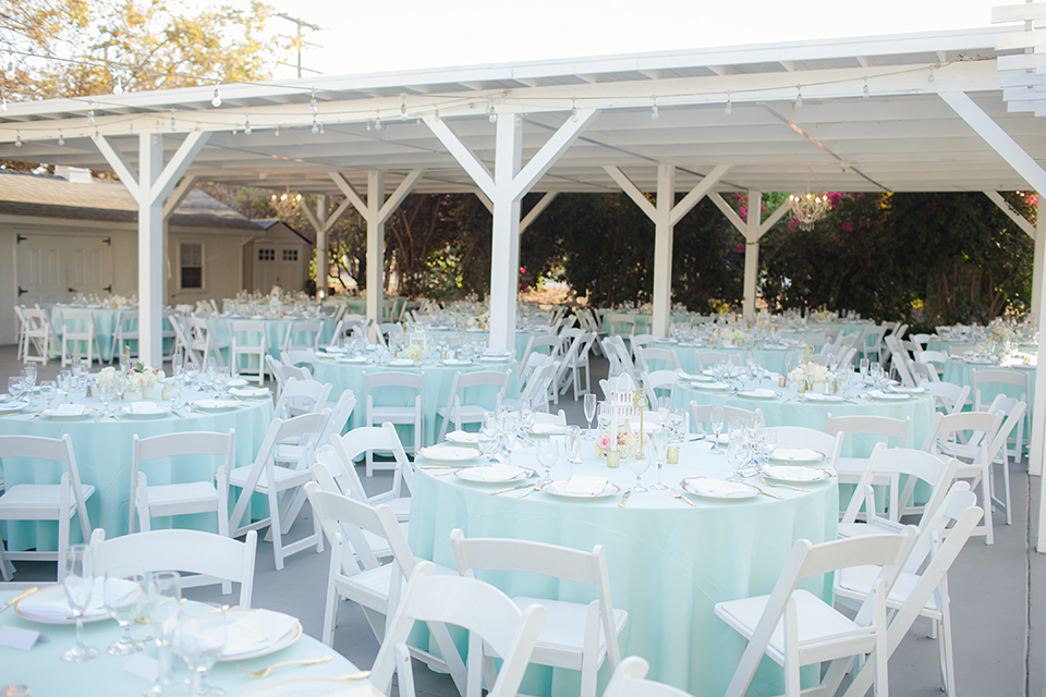 Orange county outdoor summer wedding at the heritage museum table set up with mint green table linens and white chairs with white flower centerpiece decor with glassware and white place settings with gold silverware and candles
