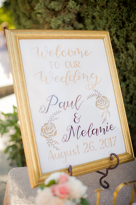 Orange county outdoor summer wedding at the heritage museum wedding welcome sign with white sign and gold frame with gold cursive writing on stand wedding photo idea for ceremony decor