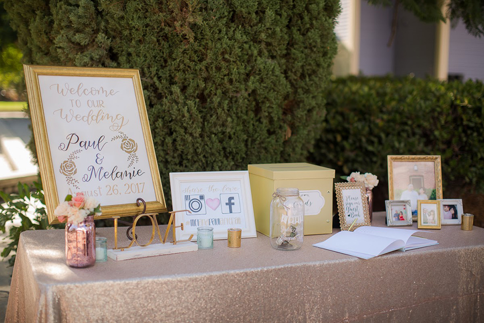 Orange county outdoor summer wedding at the heritage museum wedding welcome sign with white sign and gold frame with gold cursive writing on stand wedding photo idea for ceremony decor on table with card box and gifts