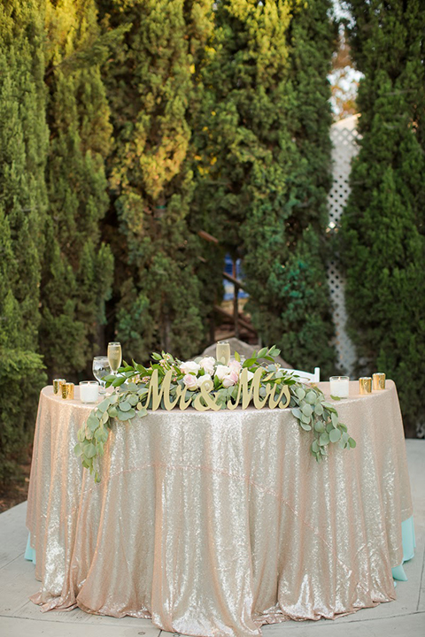 Orange county outdoor summer wedding at the heritage museum wedding reception sweetheart table with champagne sequined table linen and greenery floral decor with white place settings and glassware with gold mr and mrs signs