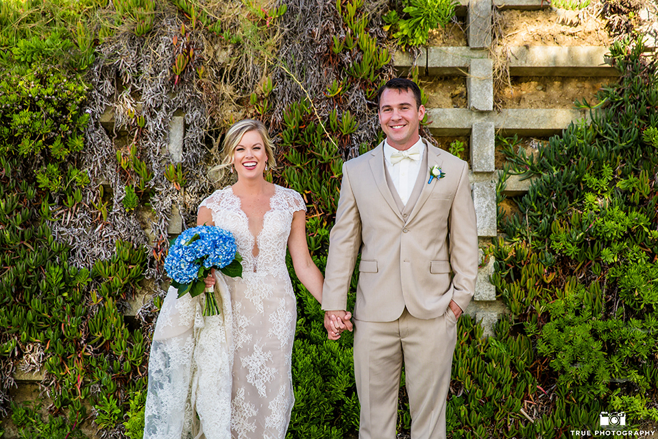 San diego outdoor wedding at the l auberge bride form fitting lace gown with short sleeves and plunging neckline with low back design and groom tan suit with matching vest and white dress shirt with a tan bow tie and brown shoes with a white and blue floral boutonniere holding hands and bride holding blue floral bridal bouquet