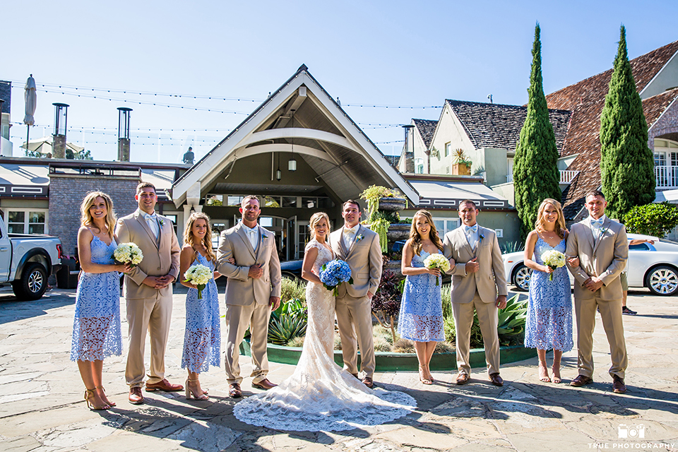 San diego outdoor wedding at the l auberge bride form fitting lace gown with short sleeves and plunging neckline with low back design and groom tan suit with matching vest and white dress shirt with a tan bow tie and brown shoes with a white and blue floral boutonniere with wedding party bridesmaids short blue lace dresses and groomsmen tan suits with tan bow ties