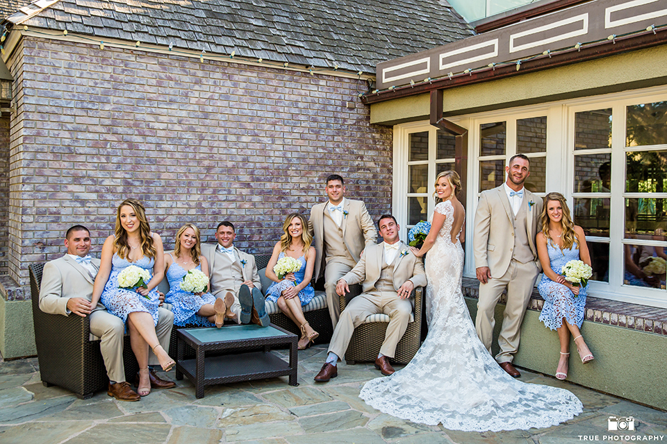 San diego outdoor wedding at the l auberge bride form fitting lace gown with short sleeves and plunging neckline with low back design and groom tan suit with matching vest and white dress shirt with a tan bow tie and brown shoes with a white and blue floral boutonniere sitting with wedding party bridesmaids short blue lace dresses and groomsmen tan suits with tan bow ties