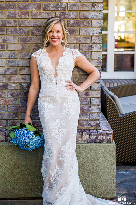 San diego outdoor wedding at the l auberge bride form fitting lace gown with short sleeves and plunging neckline with low back design holding blue floral bridal bouquet