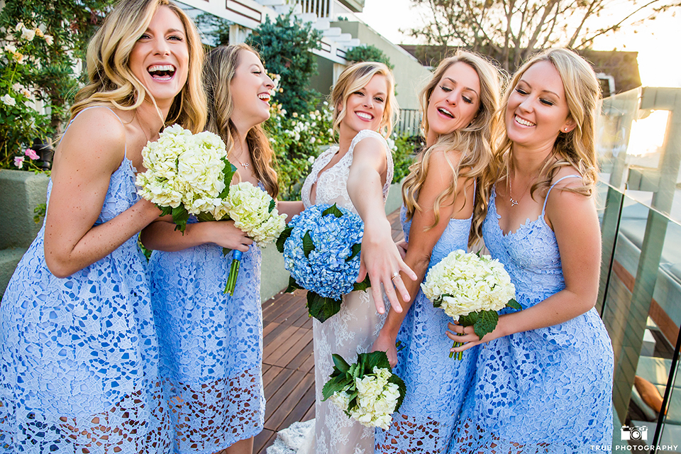 San diego outdoor wedding at the l auberge bride form fitting lace gown with short sleeves and plunging neckline with low back design holding blue floral bridal bouquet with bridesmaids short blue lace dresses showing off wedding ring