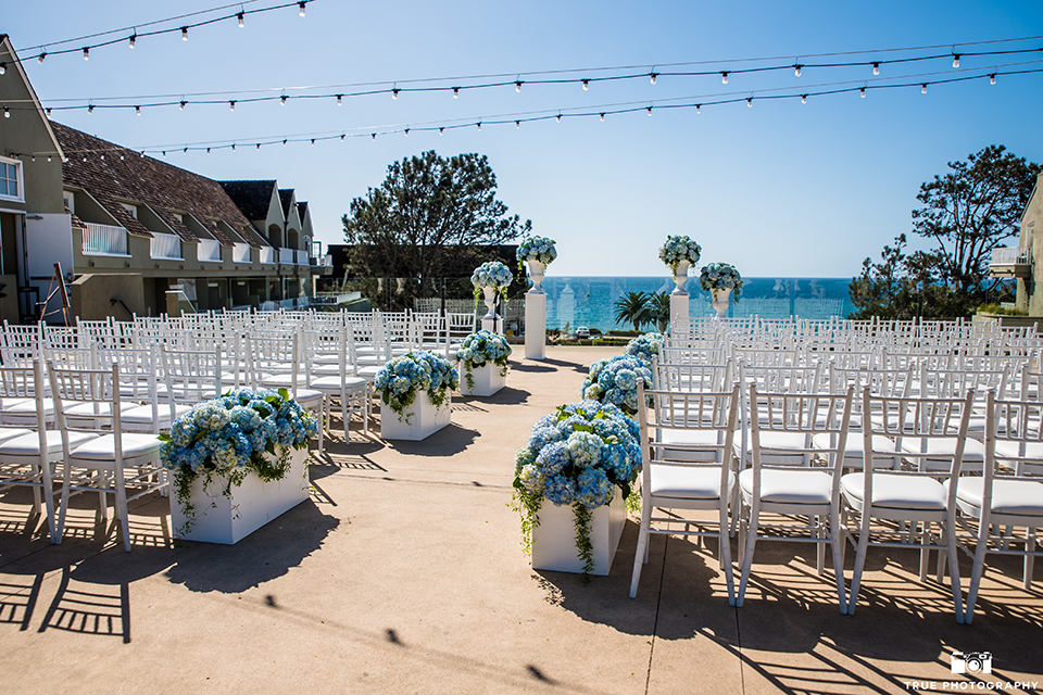 San diego outdoor wedding at l auberge ceremony set up with white chairs and white and blue flowers along aisle with hanging lights and white pillars with flower decor wedding photo idea for ceremony