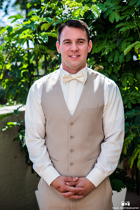 San diego outdoor wedding at the l auberge groom tan notch lapel suit with a matching vest and white dress shirt with a tan bow tie and white and blue floral boutonniere standing with hands folded