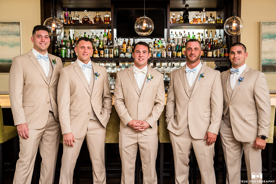 San diego outdoor wedding at the l auberge groom tan notch lapel suit with a matching vest and white dress shirt with a tan bow tie and white and blue floral boutonniere with groomsmen tan suits with light blue bow ties