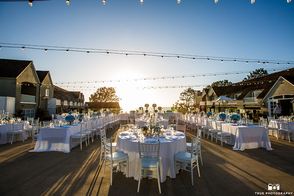 San diego outdoor wedding at l auberge reception table set up white table linen with white place settings and white chiavari chairs and blue flower centerpiece decor with tall glass candle vases and hanging lights