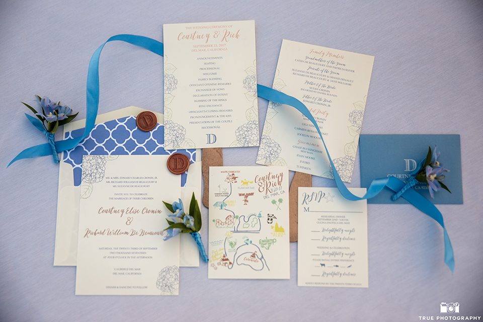 San diego outdoor wedding at l auberge wedding invitations white with blue writing and blue ribbon decor with white and blue envelope on light blue linen background wedding photo idea for invitations