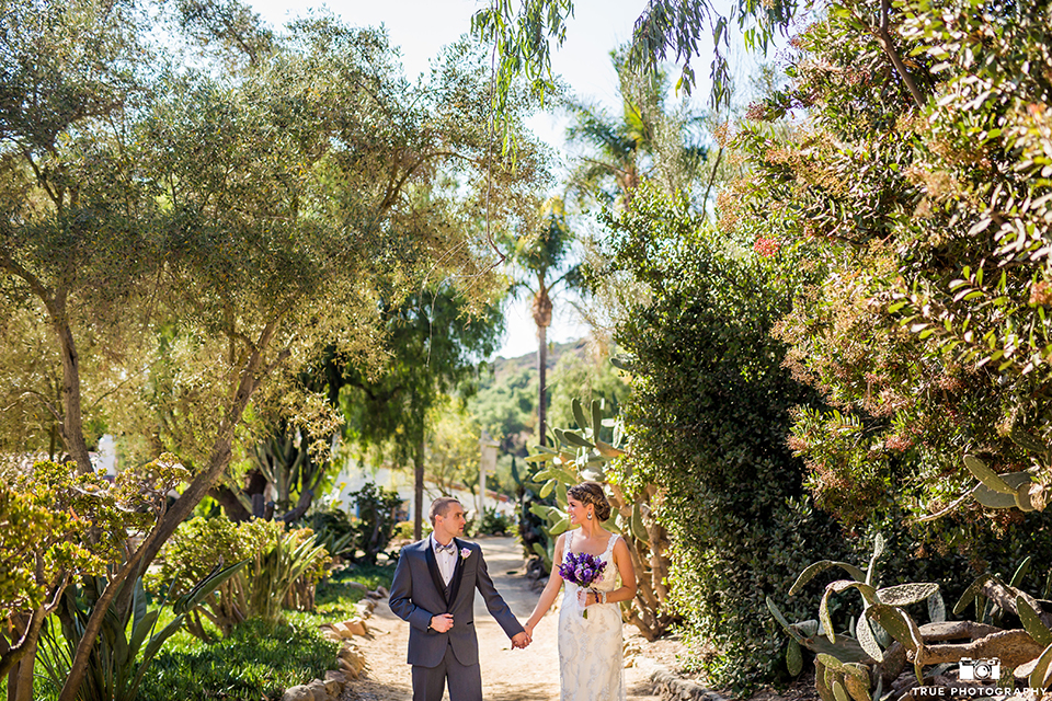 San diego outdoor wedding at leo carillo ranch bride form fitting gown with a sweetheart neckline with thin straps and beaded detail on bodice with groom charcoal grey tuxedo with a black shawl and matching vest with a white dress shirt and plaid bow tie with a white floral boutonniere holding hands and bride holding purple floral bridal bouquet