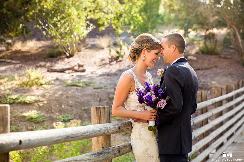 San diego outdoor wedding at leo carillo ranch bride form fitting gown with a sweetheart neckline with thin straps and beaded detail on bodice with groom charcoal grey tuxedo with a black shawl and matching vest with a white dress shirt and plaid bow tie with a white floral boutonniere hugging and bride holding purple floral bridal bouquet