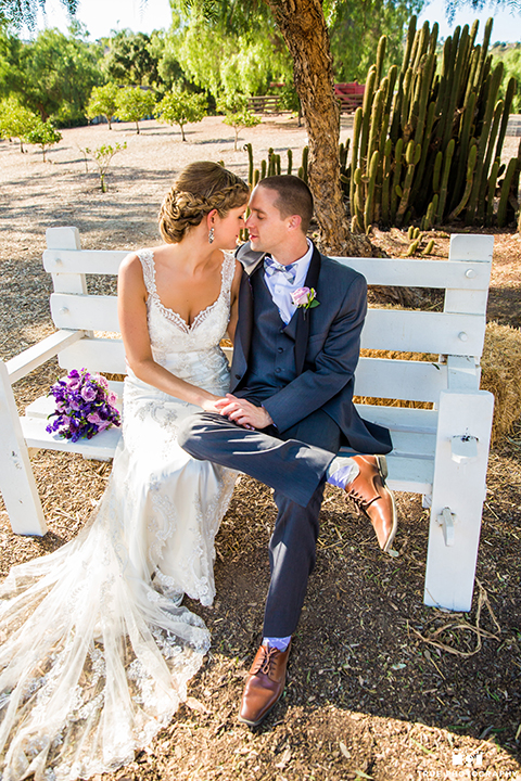 San diego outdoor wedding at leo carillo ranch bride form fitting gown with a sweetheart neckline with thin straps and beaded detail on bodice with groom charcoal grey tuxedo with a black shawl and matching vest with a white dress shirt and plaid bow tie with a white floral boutonniere sitting on white bench with purple floral bridal bouquet